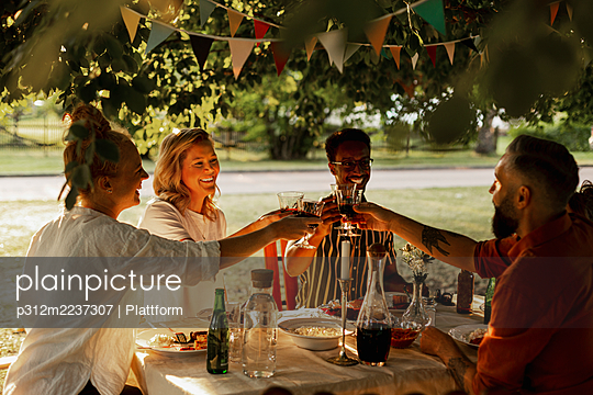 Happy friends having meal in garden - p312m2237307 by Plattform