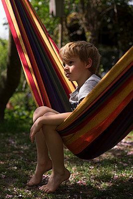 Boy sitting in a hammock, stay at home due to Covid-19 - p1498m2183724 by Nina King