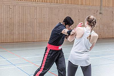 Female boxer sparring with coach in sports hall - p300m2144494 von Stefanie Baum