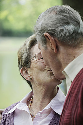 Germany, Cologne, Senior couple kissing  in park - p300m2207257 by Jan Tepass