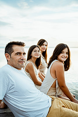 Smiling parents sitting with children at jetty against lake and sky - p300m2241059 by Rafa Cortés