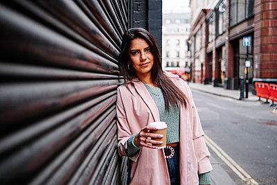 Smiling woman with coffee cup leaning on shutter in city - p300m2273682 by Angel Santana Garcia
