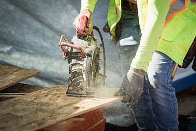 Construction worker using saw on plywood - p301m2296786 by Peter Stark