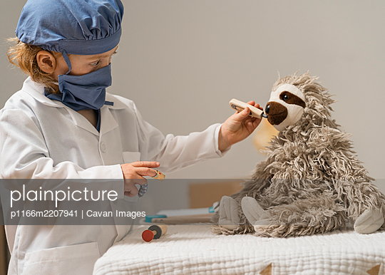 young child in medical PPE examines a plush toy sloth and takes it's temperature with thermometer - p1166m2207941 by Cavan Images