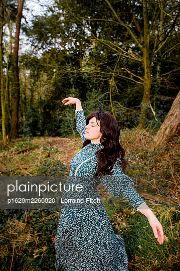 Young woman in green dress dancing in the forest - p1628m2260820 by Lorraine Fitch