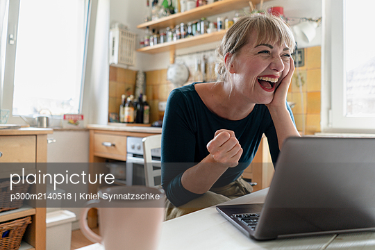 Portrait of woman sitting in the kitchen with laptop crying for joy - p300m2140518 by Kniel Synnatzschke