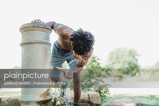 Young man during workout, drinking from fountain in a park