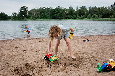 brother and sister playing at the beach with toys in summer - p1166m2129972 by Cavan Images