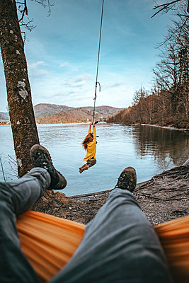Young woman on a swing next to Bohinj Lake in Slovenia - p1455m2077136 by Ingmar Wein