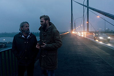 Father and son meeting on bridge, discussing business - p300m1537382 by Kniel Synnatzschke