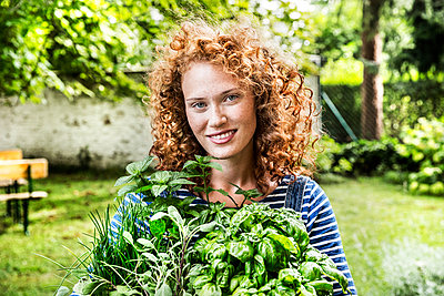 Portrait of young woman with fresh herbs in garden - p300m2029189 by Jo Kirchherr