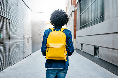 Back view of young man with yellow backpack on E-Scooter in the city - p300m2114547 by Josep Rovirosa