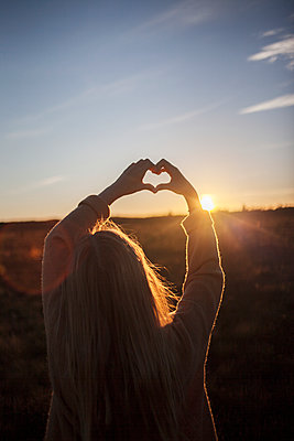 Girl making heart sign at sunset - p312m1470788 by Christina Strehlow
