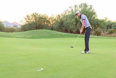 Caucasian golfer putting on golf course - p555m1472887 by Kolostock