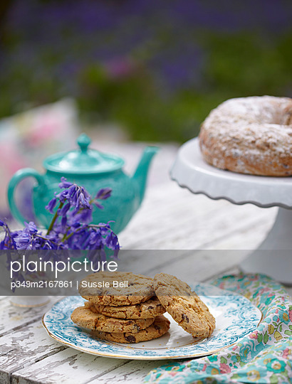 Biscuits and cake with bluebells and teapot  (Hyacinthoides non-scripta). - p349m2167861 by Sussie Bell