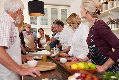 Active senior friends watching chef in pizza cooking class - p1023m1583936 by Trevor Adeline