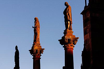 Antike Skulpturen auf Stelen vor blauem Himmel - p1065m948660 von KNSY Bande