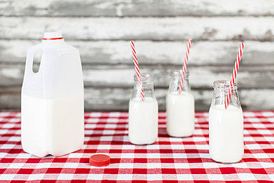 Milk bottles and jug with striped straws on tablecloth - p1094m1015326 by Patrick Strattner