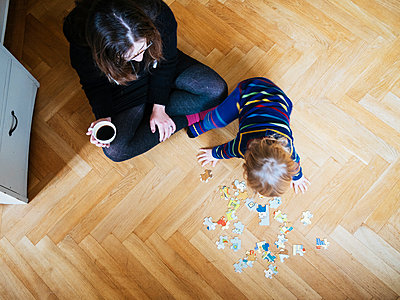 High angle view of woman holding coffee cup while looking at baby girl with puzzle pieces - p1185m1016068f by Astrakan