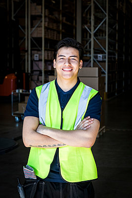 Portrait of smiling young male warehouse worker standing with arms crossed at storage room - p426m2018816 by Maskot