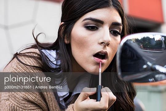 Portrait of young woman applying lipstick outdoors - p300m2131651 by Andrés Benitez