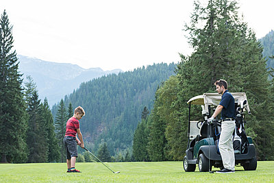 Father assisting his son to play golf in the course - p1315m1565177 by Wavebreak