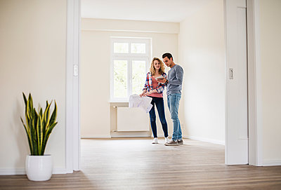 Young couple in new home with tablet and ground plan - p300m1460025 by Uwe Umstätter