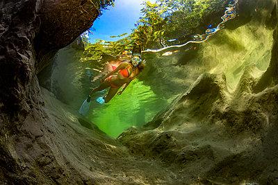 Austria, Salzkammergut, young woman snorkeling in mountain river Weissenbach - p300m2104135 by Herbert Meyrl