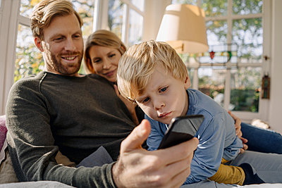 Happy family using cell phone in sunroom at home - p300m2166638 by Kniel Synnatzschke