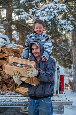 Caucasian father and son carrying firewood from truck - p555m1232040 by Steve Smith