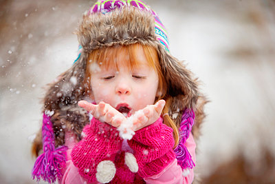 Caucasian girl blowing handful of snow - p555m1311401 by Shestock