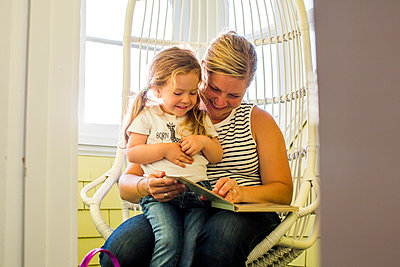 Caucasian mother reading book to daughter on lap - p555m1532438 by Adam Hester