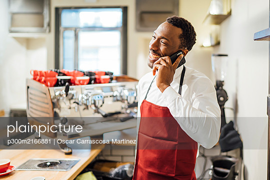Happy barista on the phone in a coffee shop - p300m2166881 by Oscar Carrascosa Martinez