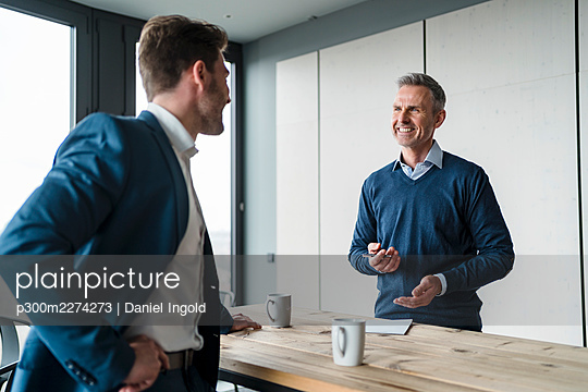 Smiling business people discussing at table in office cafe - p300m2274273 by Daniel Ingold