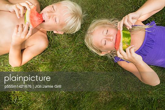 Caucasian children eating watermelon on lawn - p555m1421676 by JGI/Jamie Grill