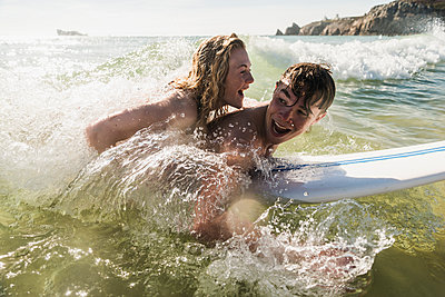 Teenage couple having fun on surfboard in the sea - p300m1189416 by Uwe Umstätter