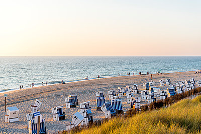 Germany, Schleswig-Holstein, Sylt, beach and empty hooded beach chairs at sunset - p300m1587380 by Ega Birk