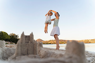Sand castle and happy mother with daughter on the beach - p300m2143492 by Daniel Ingold