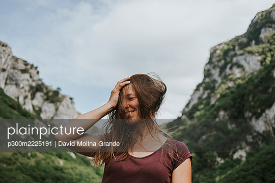 Happy female trekker with tousled long brown hair against mountain range - p300m2225191 by David Molina Grande