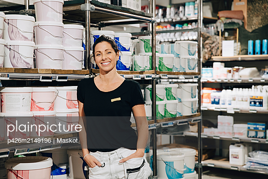 Portrait of smiling sales woman with hands in pocket standing in store - p426m2149196 by Maskot