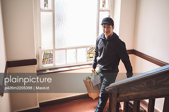 High angle portrait of smiling delivery man with package against window - p426m2205398 by Maskot