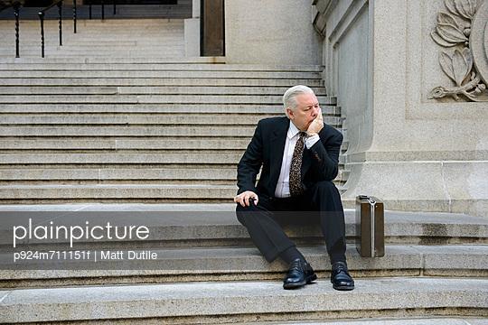 Sad businessman on steps - p924m711151f by Matt Dutile