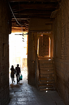Two people walking through lane in Jaisalmer - p1259m1111447 by J.-P. Westermann