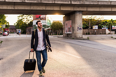 Young man on the move with skateboard, rolling suitcase and headphones - p300m1460434 by Uwe Umstätter