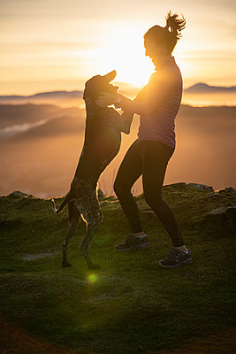 Woman playing with dog on hill during sunrise - p300m2282811 by SERGIO NIEVAS