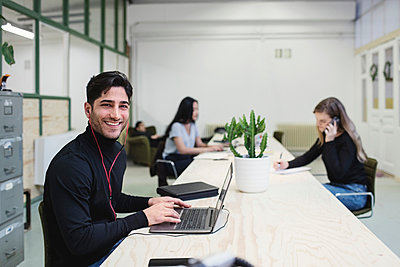 Portrait of happy young man sitting at desk with colleagues working in background - p426m1407199 by Maskot
