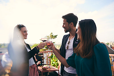 Smiling friends toasting drinks while partying on terrace - p426m2074325 by Maskot