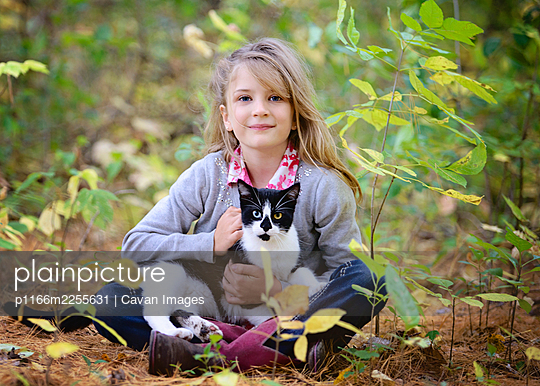 Young blond girl sitting in the woods with black and white cat in lap. - p1166m2255631 by Cavan Images