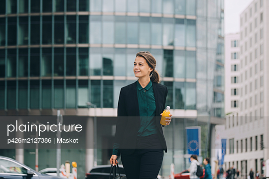 Confident businesswoman looking away while walking in city - p426m2127386 by Maskot