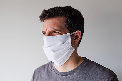 Man wearing homemade cloth face mask during Covid 19 pandemic. - p1166m2174101 by Cavan Images